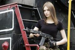 黑T恤杉的女孩有枪的,摆在机车附近 免版税库存图片