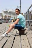 T恤杉的年轻人坐系船柱在有近障碍的木码头在小游艇船坞旅馆 免版税库存图片
