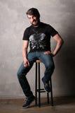 黑T恤杉的有胡子的人有的坐高凳 灰色 免版税库存图片