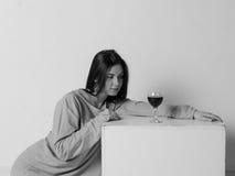 T恤杉的美丽的女孩在一个正方形的立方体附近,与一杯酒 免版税库存照片