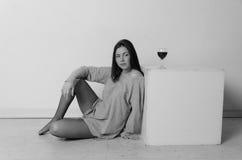 T恤杉的美丽的女孩在一个正方形的立方体附近,与一杯酒 免版税图库摄影