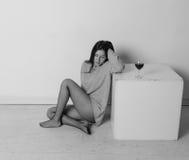 T恤杉的美丽的女孩在一个正方形的立方体附近,与一杯酒 库存照片