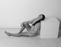 T恤杉的美丽的女孩在立方体,正方形附近 免版税库存图片