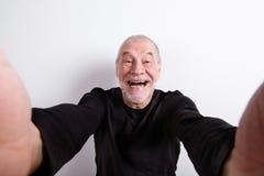 黑T恤杉的老人,采取selfie,演播室射击 库存照片