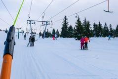 T酒吧滑雪电缆车的滑雪者在Szklarska Poreba,波兰 免版税库存图片