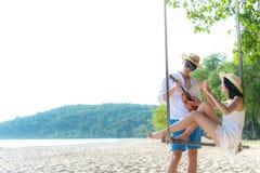 亚洲浪漫夫妇坐在绳索摇摆放松和幸福的海海滩为假日 蜜月在夏天t一起放松 图库摄影