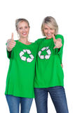 穿绿色回收的T恤杉的两名愉快的妇女给赞许 库存图片