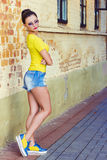 有黑发的美丽的性感的女孩在支持砖墙的太阳镜、短裤和黄色T恤杉 免版税图库摄影