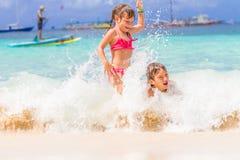 两个年轻愉快的孩子-女孩和男孩-获得乐趣在水中, t 免版税图库摄影