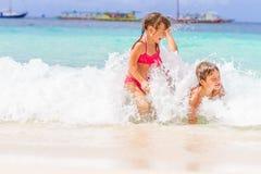 两个年轻愉快的孩子-女孩和男孩-获得乐趣在水中, t 免版税库存照片