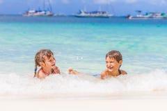 两个年轻愉快的孩子-女孩和男孩-获得乐趣在水中, t 免版税库存图片