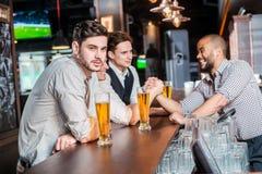 可爱的晚上 获得三个朋友的人喝啤酒和乐趣t 免版税库存照片