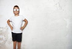 男孩佩带的白色T恤杉,短缺在墙壁上的立场 库存图片