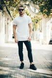 有胡子的人佩带的白色空白的T恤杉和蓝色 免版税图库摄影