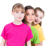 五颜六色的T恤杉的三个逗人喜爱的矮小的逗人喜爱的微笑的女孩 免版税库存照片
