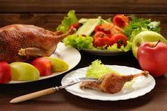 烤鸭子服务与新鲜蔬菜和苹果在木t 库存图片