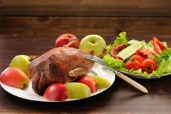 烤鸭子服务与新鲜蔬菜和苹果在木t 库存照片