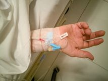 T adult women 60s with saline at C-line or A-line on a ypung adult patient hand on bed in intensive care unit ICU shock room royalty free stock photography