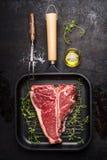 T-ben biff på att steka gallerpannan med gaffeln, olja och att krydda för kött på mörk lantlig bakgrund Royaltyfri Bild