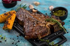 T-bone beef stake served on a cutting board, view from above royalty free stock images