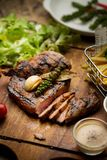 T-Bone Beef Steak on wooden board.  Beef Steak Dinner and French. Fries Royalty Free Stock Photo