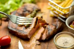 T-Bone Beef Steak on wooden board.  Beef Steak Dinner and French. Fries Royalty Free Stock Photos