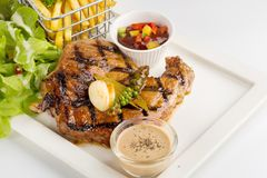 T-Bone Beef Steak on wooden board.  Beef Steak Dinner and French. Fries Royalty Free Stock Image