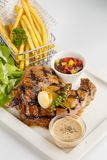 T-Bone Beef Steak on wooden board.  Beef Steak Dinner and French. Fries Stock Photography