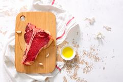 T-bone raw steak on a kitchen table surface, view from above. T-bone raw steak on a kitchen table surface ready to be cooked, view from above, space for a text stock photo