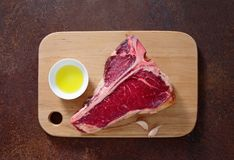 T-bone raw steak on a kitchen table surface, view from above. T-bone raw steak on a kitchen table surface ready to be cooked, view from above royalty free stock images