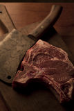 T-bone roast beef steak with a vintage cleaver on a cutting boar. T-bone roast beef steak with a vintage cleaver royalty free stock images