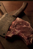 T-bone roast beef steak with a vintage cleaver on a cutting boar. T-bone roast beef steak with a vintage cleaver stock image