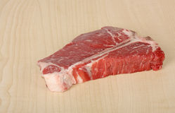T-bone Steak. Raw t-bone steak on a cutting board Royalty Free Stock Photography