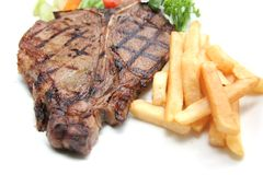 T-bone steak. On the plate with french fries Royalty Free Stock Photos