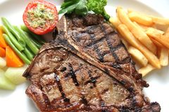 T-bone steak. On the plate with french fries Stock Image
