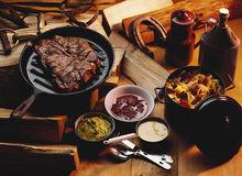 T-bone steak. In grill pan, three sauces and a stew Royalty Free Stock Photography