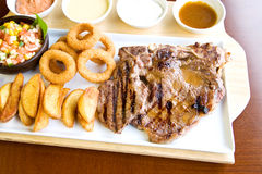 T-bone steak. With sauce and grilled vegetables Royalty Free Stock Photos