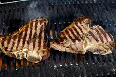 T-bone steak on bbq fire. Delicious T-bone steak on a BBQ. Image taken as a closeup outside Stock Photos
