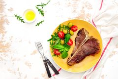 T-bone steak ready to eat, served on a plate, view from above. T-bone steak cooked and ready to eat, served on a plate, overhead view stock image