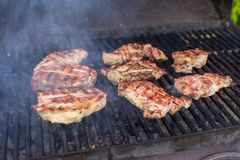 T-bone steak cooking on an open flame grill Stock Photo
