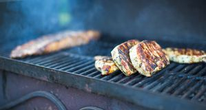 T-bone steak cooking on an open flame grill Stock Photography