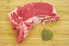 T-bone steak on cutting board with seasoning Stock Image