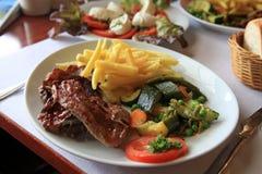 T-Bone Steak. Dinner plate with t-bone steak, potato and vegetables. Selective focus Royalty Free Stock Photos