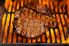 T-Bone steak. A t- bone steak flame broiled on a barbecue, shallow depth of field Royalty Free Stock Photo
