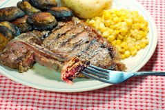 T bone steak on a fork. Barbecue T bone steak on a fork with corn mushrooms and a baked potato with focus on the meat on the fork Royalty Free Stock Images