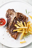 T-Bone Steak with french fries. T-Bone Steak with Salted french fries on white plate on blue wooden background Stock Images