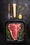 T-bone Steak on frying grill pan with meat fork, oil and seasoning on dark rustic background royalty free stock image