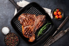 T-bone steak. Grilled T-bone steak and red wine glass on stone table. Top view Stock Photo