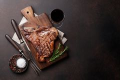 T-bone steak. Grilled T-bone steak and red wine glass on stone table. Top view with copy space royalty free stock image