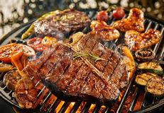 T-bone steak grilling over a portable barbecue. Outdoors in summer with garlic, tomato, rump steak, chicken wings and baby narrow Stock Images